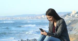 Συγκινημένος έφηβος που διαβάζει τις καλές ειδήσεις στην παραλία απόθεμα βίντεο