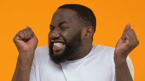 Συγκινημένος αφροαμερικανός τύπος που αισθάνεται την ευτυχή επιτυχία εορτασμού, τύχη επιτεύγματος φιλμ μικρού μήκους