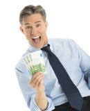 Συγκινημένος επιχειρηματίας που παρουσιάζει ευρο- τραπεζογραμμάτια Στοκ Εικόνες