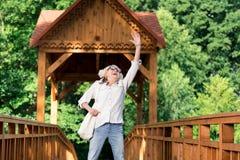 Συγκινημένος θετικός συνταξιούχος που βάζει το χέρι της επάνω και που πηδά στοκ φωτογραφίες με δικαίωμα ελεύθερης χρήσης