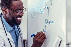 Συγκινημένος ιατρικός εργαζόμενος αφροαμερικάνων που σύρει το χημικό σχέδιο Στοκ φωτογραφία με δικαίωμα ελεύθερης χρήσης