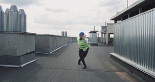 Συγκινημένος μηχανικός στη στέγη του εργοτάξιου οικοδομής που χορεύει χαρισματική μπροστά από τη κάμερα έχει μια ασφάλεια απόθεμα βίντεο