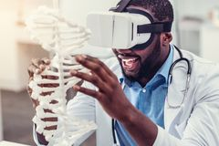 Συγκινημένος νέος επαγγελματίας στα γυαλιά εικονικής πραγματικότητας σχετικά με το πρότυπο DNA Στοκ Εικόνα