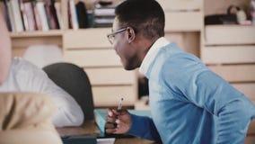 Συγκινημένος νέος επιχειρηματίας αφροαμερικάνων που εκφράζει τη χαρούμενη συγκίνηση στην επιχειρησιακή συνεδρίαση στο σύγχρονο γρ απόθεμα βίντεο