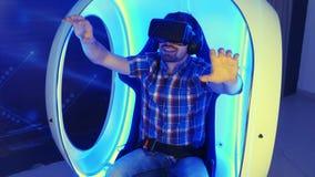 Συγκινημένος νεαρός άνδρας που απολαμβάνει την έλξη εικονικής πραγματικότητας σε μια καρέκλα vr απόθεμα βίντεο