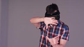 Συγκινημένος νεαρός άνδρας στα γυαλιά VR που ενεργά στον αέρα απόθεμα βίντεο