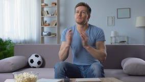 Συγκινημένος οπαδός ποδοσφαίρου που διασχίζει τα δάχτυλα για την καλή τύχη, που υποστηρίζει τη εθνική ομάδα απόθεμα βίντεο