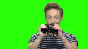 Συγκινημένος περίεργος έφηβος που κοιτάζει μέσω των διοπτρών φιλμ μικρού μήκους