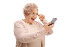 Συγκινημένος πρεσβύτερος που εξετάζει ένα τηλέφωνο στοκ φωτογραφία