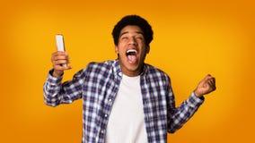 Συγκινημένος σπουδαστής με τη νίκη τηλεφωνικού εορτασμού, υπόβαθρο στούντιο στοκ φωτογραφία