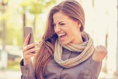 Συγκινημένος σπουδαστής που διαβάζει τις καλές ειδήσεις στο κινητό τηλέφωνο υπαίθρια μια θερμή ημέρα φθινοπώρου στοκ φωτογραφία με δικαίωμα ελεύθερης χρήσης