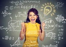 Συγκινημένος σπουδαστής με τη λάμπα φωτός ιδέας και τύποι μαθηματικών και επιστήμης στον πίνακα Στοκ Φωτογραφία