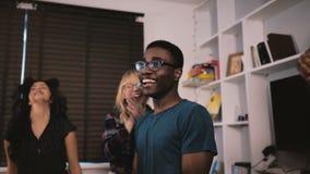 Συγκινημένος τύπος αφροαμερικάνων που χορεύει με τους multiethnic φίλους στον περιστασιακό πυροβολισμό βράσης γιορτών γενεθλίων σ απόθεμα βίντεο