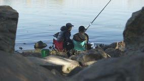 Συγκινημένος ψαράς που τραβά τη ράβδο αλιείας με τα μεγάλα ψάρια, που περιστρέφει το εξέλικτρο, διασκέδαση απόθεμα βίντεο