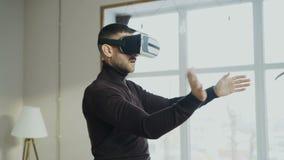 Συγκινημένο άτομο με την κάσκα εικονικής πραγματικότητας που παίζει το τηλεοπτικό παιχνίδι 360 στο σπίτι απόθεμα βίντεο