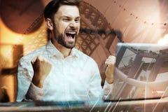 Συγκινημένο άτομο που αυξάνει τις πυγμές στο θρίαμβο ενώ έχοντας την τηλεοπτική κλήση Στοκ Εικόνα