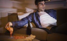 Συγκινημένο άτομο που τρώει την πίτσα και που προσέχει τον κινηματογράφο στο lap-top Στοκ Φωτογραφίες