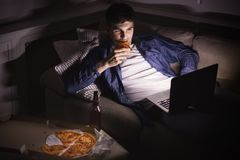 Συγκινημένο άτομο που τρώει την πίτσα και που προσέχει τον κινηματογράφο στο lap-top Στοκ Εικόνες