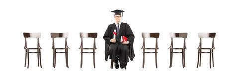 Συγκινημένο δίπλωμα εκμετάλλευσης φοιτητών πανεπιστημίου, που κάθεται στην ξύλινη καρέκλα Στοκ Εικόνα