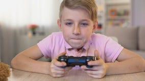 Συγκινημένο αρσενικό παιδί που παίρνει το πηδάλιο από τον πίνακα, παίζοντας τηλεοπτικό το παιχνίδι, ψυχαγωγία φιλμ μικρού μήκους