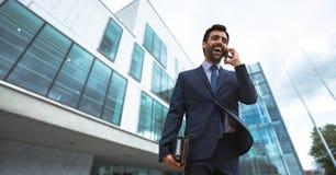 Συγκινημένο επιχειρησιακό άτομο που μιλά στο τηλέφωνο ενάντια στην οικοδόμηση του υποβάθρου Στοκ Εικόνες
