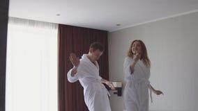 Συγκινημένο ευτυχές ζεύγος που πηδά και που χορεύει στο κρεβάτι μετά από να φθάσει στο κρεβάτι ξενοδοχείων στο διαμέρισμα beachsi φιλμ μικρού μήκους