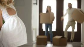 Συγκινημένο ζεύγος με τα παιδιά και τα κιβώτια που κινούνται στο καινούργιο σπίτι φιλμ μικρού μήκους