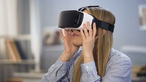Συγκινημένο θηλυκό gamer που κοιτάζει γύρω στα γυαλιά εικονικής πραγματικότητας, καινοτομία απόθεμα βίντεο