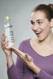 Συγκινημένο κορίτσι της δεκαετίας του '20 που παρουσιάζει μπουκάλι του φρέσκου zesty νερού στοκ εικόνες με δικαίωμα ελεύθερης χρήσης
