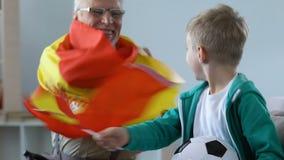 Συγκινημένο μικρό αγόρι με τον αγώνα ποδοσφαίρου προσοχής grandpa, ανεμιστήρες που κυματίζει τη σημαία της Ισπανίας απόθεμα βίντεο