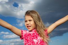 Συγκινημένο νέο κορίτσι ενάντια στο νεφελώδη ουρανό στοκ φωτογραφία