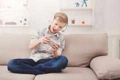 Συγκινημένο παίζοντας παιχνίδι online εφήβων στο σπίτι Στοκ Εικόνες