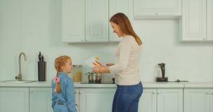 Συγκινημένο παιδί που παρουσιάζει σχέδιο στο πολυάσχολο mum στην κουζίνα απόθεμα βίντεο