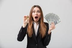 Συγκλονισμένα businesslady χρυσά bitcoin και δολάρια εκμετάλλευσης στα χέρια που απομονώνονται Στοκ Φωτογραφία
