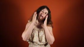 Συγκλονισμένη έκπληκτη αρκετά νέα γυναίκα σχετικά με το πρόσωπό της στο πορτοκαλί υπόβαθρο απόθεμα βίντεο