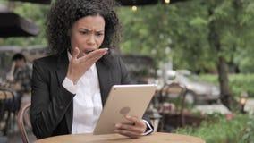 Συγκλονισμένη αφρικανική γυναίκα που ανατρέπεται από την απώλεια στην ταμπλέτα, που κάθεται στον υπαίθριο καφέ απόθεμα βίντεο