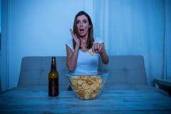 Συγκλονισμένη γυναίκα που προσέχει τη TV Στοκ εικόνες με δικαίωμα ελεύθερης χρήσης