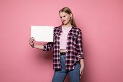 Συγκλονισμένη νέα γυναίκα στα περιστασιακά ενδύματα, που κρατούν το άσπρο κενό κενό για το κείμενό σας στοκ φωτογραφία με δικαίωμα ελεύθερης χρήσης