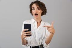 Συγκλονισμένη νέα τοποθέτηση επιχειρησιακών γυναικών πέρα από το γκρίζο υπόβαθρο τοίχων που χρησιμοποιεί κινητό τηλεφωνικό να κου στοκ φωτογραφίες με δικαίωμα ελεύθερης χρήσης