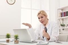 Συγκλονισμένος γιατρός που εξετάζει το lap-top στοκ εικόνες