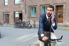 Συγκλονισμένος επιχειρηματίας που οδηγά ένα ποδήλατο μιλώντας στο τηλέφωνο Στοκ Φωτογραφίες