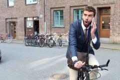 Συγκλονισμένος επιχειρηματίας που οδηγά ένα ποδήλατο μιλώντας στο τηλέφωνο Στοκ Εικόνα