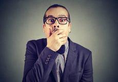 Συγκλονισμένος νεαρός άνδρας που καλύπτει το στόμα του με τα χέρια στοκ εικόνα με δικαίωμα ελεύθερης χρήσης