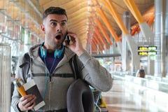 Συγκλονισμένος ταξιδιώτης που παίρνει ένα απροσδόκητο τηλεφώνημα στοκ φωτογραφία