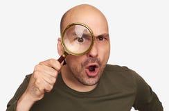 Συγκλονισμένος φαλακρός τύπος που κοιτάζει μέσω της ενίσχυσης - γυαλί Στοκ Εικόνα