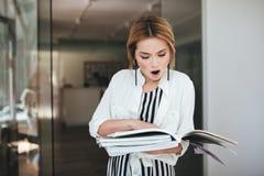 Συγκλονισμένο κορίτσι στο γδυμένο φόρεμα και το άσπρο πουκάμισο που στέκονται κοντά στην πόρτα με τα περιοδικά στα χέρια στοκ φωτογραφία με δικαίωμα ελεύθερης χρήσης