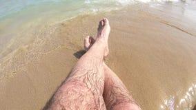 Συγκομιδή των αρσενικών ποδιών στην παραλία απόθεμα βίντεο