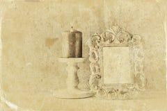 Συγκρατημένη εικόνα του εκλεκτής ποιότητας παλαιού κλασσικού πλαισίου και του καίγοντας κεριού στον ξύλινο πίνακα αναδρομική φιλτ Στοκ εικόνες με δικαίωμα ελεύθερης χρήσης