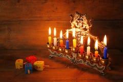 Συγκρατημένη εικόνα των εβραϊκών διακοπών Hanukkah με το menorah (παραδοσιακά κηροπήγια), donuts και τα ξύλινα dreidels (περιστρε Στοκ Φωτογραφίες