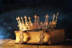συγκρατημένος της κορώνας βασίλισσας/βασιλιάδων στο παλαιό βιβλίο Τρύγος που φιλτράρεται μεσαιωνική περίοδος φαντασίας Στοκ φωτογραφία με δικαίωμα ελεύθερης χρήσης